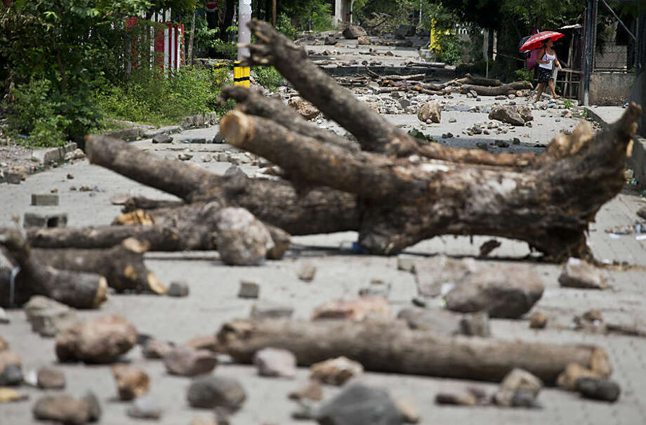 Tree trunks and rocks placed by striking miners cover a residential street in El Limon, Nicaragua, Wednesday, Oct. 7, 2015. Clashes between police and miners erupted Tuesday when police tried to remove roadblocks set up all over town by miners who have been on strike for two weeks after their top three union leaders were fired by the Canadian mine company B2Gold. According to police, one officer died in the violence. (AP Photo/Esteban Felix)
