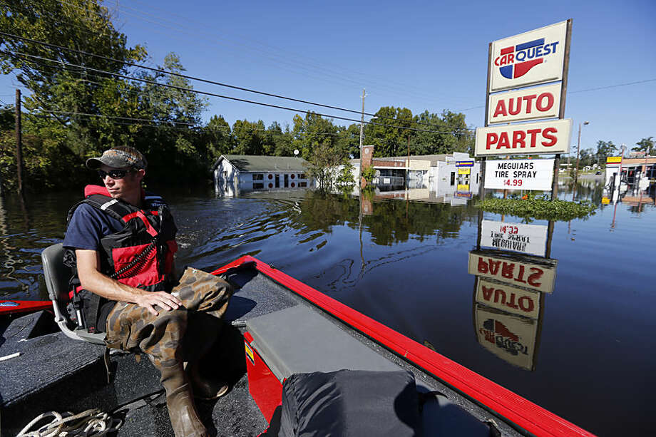 """Greg Ward, with the Kingstree Fire Department, searches for unstable propane tanks on E. Main Street in downtown Kingstree, S.C., Wednesday, Oct. 7, 2015. """"Were pretty much an island right now,"""" Ward said of his small city. (AP Photo/Mic Smith)"""