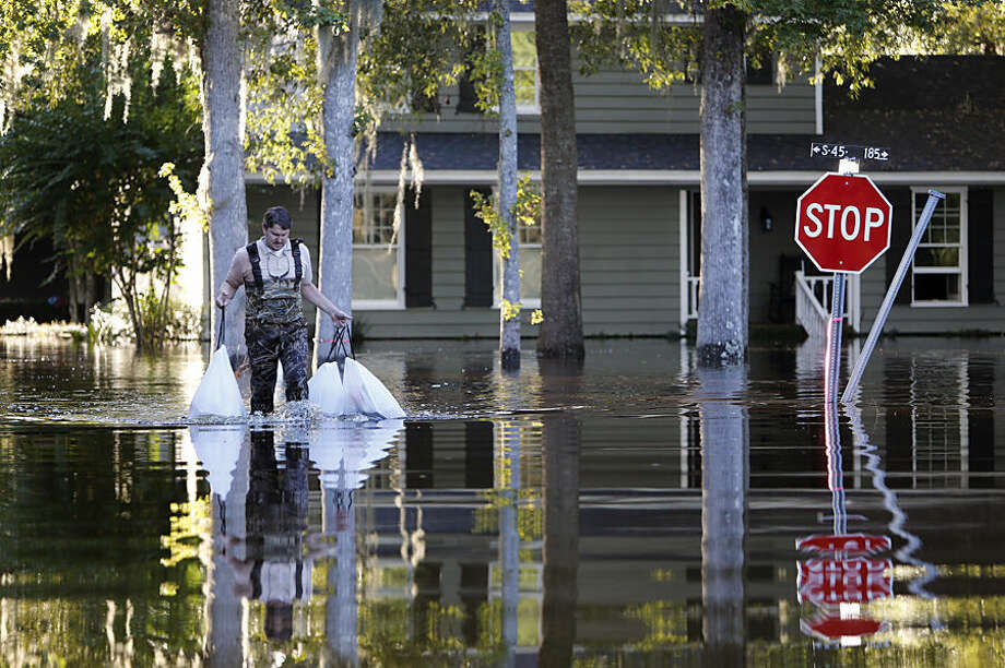 Kevin Cox wades through floodwaters by his home on Woodland Dr. in Kingstree, S.C., Wednesday, Oct. 7, 2015. Cox was removing food from the refrigerator at his home. (AP Photo/Mic Smith)