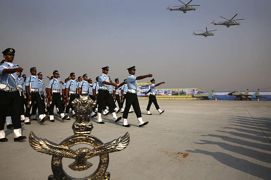 Indian Air Force Mi-35 helicopters fly above soldiers marching during the Air Force Day parade at Hindon Air Force base near New Delhi, India, Thursday, Oct. 8, 2015. Air Chief Marshal Arup Raha announced Thursday that the IAF would soon have women fighter pilots. (AP Photo/Manish Swarup)