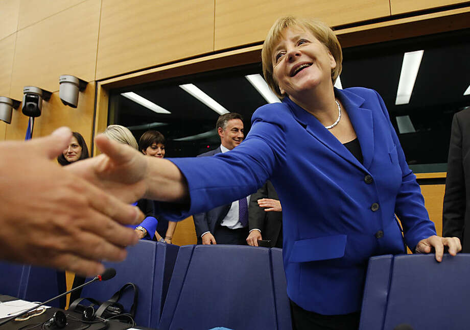 German Chancellor Angela Merkel shakes hand with delegates of her faction at the European Union Parliament in Strasbourg, eastern France, Wednesday, Oct. 7, 2015. Angela Merkel and Francois Hollande are making a historic appeal to the European Parliament on Wednesday. It's the first such joint appearance since 1989, when West German Chancellor Helmut Kohl and French President Francois Mitterrand spoke in Strasbourg days after the fall of the Berlin Wall. (AP Photo/Michael Probst)