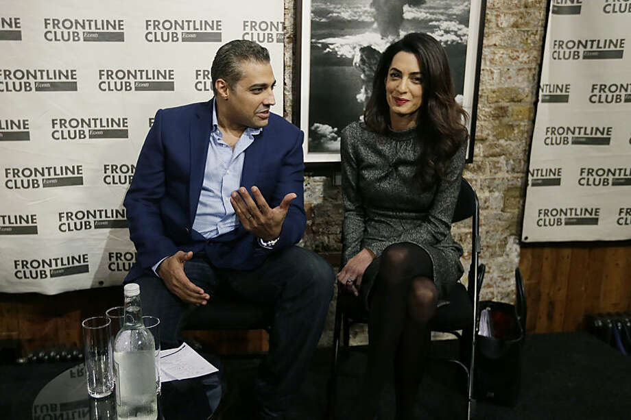 Former Al Jazeera bureau chief Mohamed Fahmy, left, with his lawyer Amal Clooney smile ahead of a talk at the Frontline Club in London, Wednesday Oct. 7, 2015. Canadian journalist Mohamed Fahmy was released from prison in Egypt on Sept. 23. (AP Photo/Tim Ireland)