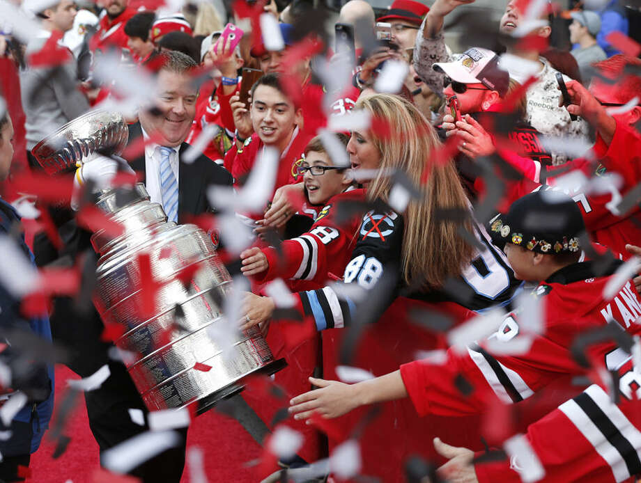 Mike Bolt, keeper of the Stanley Cup, walks the red carpet in confetti outside the United Center before an NHL hockey game between the Chicago Blackhawks and the New York Rangers, Wednesday, Oct. 7, 2015, in Chicago. (AP Photo/Charles Rex Arbogast)