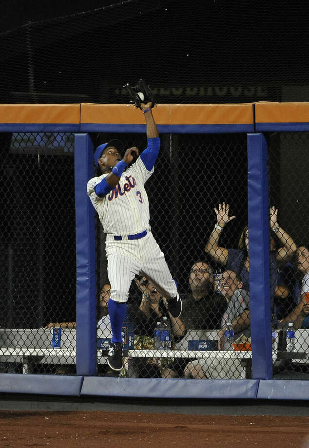 New York Mets right fielder Curtis Granderson leaps against the outfield wall to catch Philadelphia Phillies' Jimmy Rollins fly ball in the fourth inning of a baseball game at Citi Field on Saturday, Aug. 30, 2014, in New York. (AP Photo/Kathy Kmonicek)