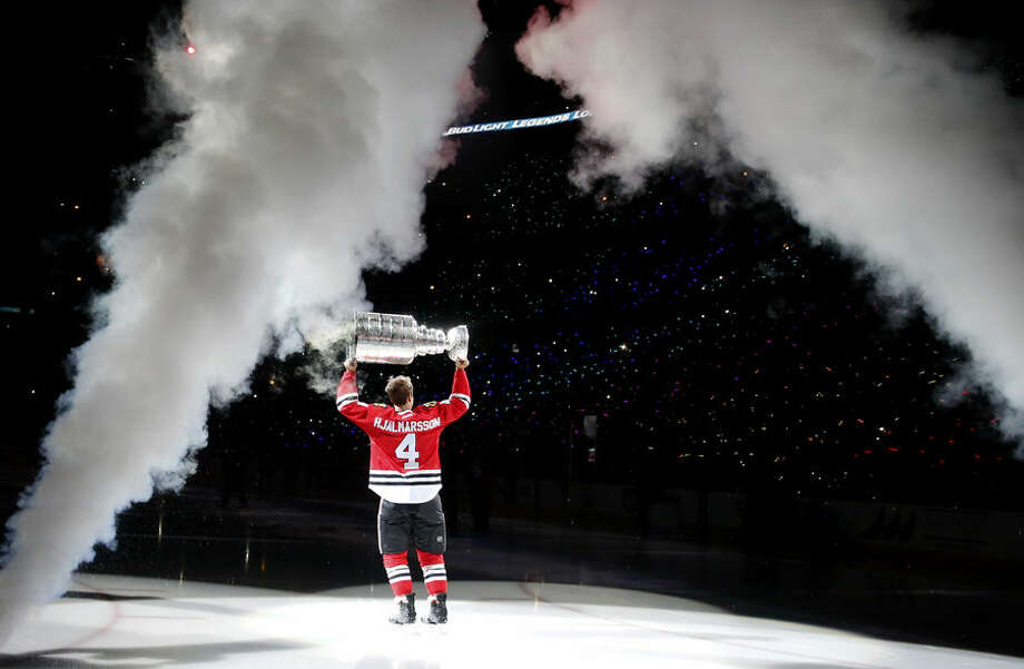 Chicago Blackhawks' Niklas Hjalmarsson skates out to center ice with the Stanley Cup during the championship banner raising ceremony before an NHL hockey game between the Blackhawks and the New York Rangers, Wednesday, Oct. 7, 2015, in Chicago. (AP Photo/Charles Rex Arbogast)