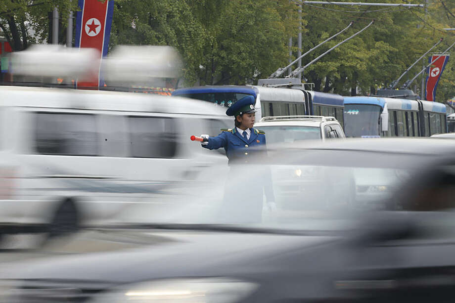 A policewoman directs traffic as the city is crowded with motorists ahead of the upcoming anniversary celebrations in Pyongyang, North Korea, Thursday, Oct. 8, 2015. The country is in high gear with preparations for the 70th anniversary of the founding of the North Korea Workers' Party on Oct. 10. (AP Photo/Charles Dharapak)