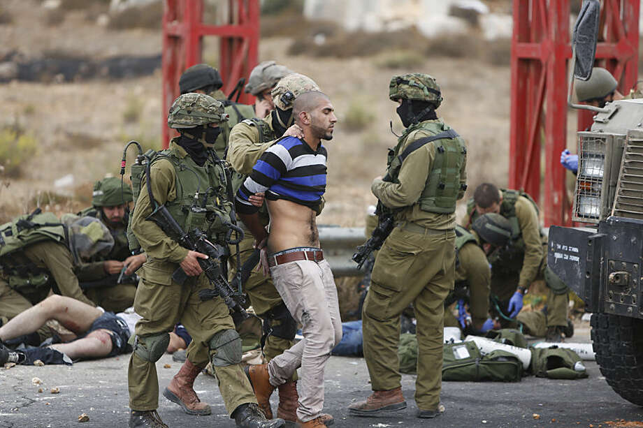 """Israeli soldiers arrest a man while others treat Palestinians wounded during clashes with the Israeli military, near Ramallah, West Bank, Wednesday, Oct. 7, 2015. Israel's prime minister says he is calling off a planned trip to Germany because of a wave of violence between Israelis and Palestinians. A statement from Benjamin Netanyahu's office Wednesday said the Israeli leader would not depart for the two-day visit so that he could """"closely monitor the situation."""" (AP Photo/Majdi Mohammed)"""