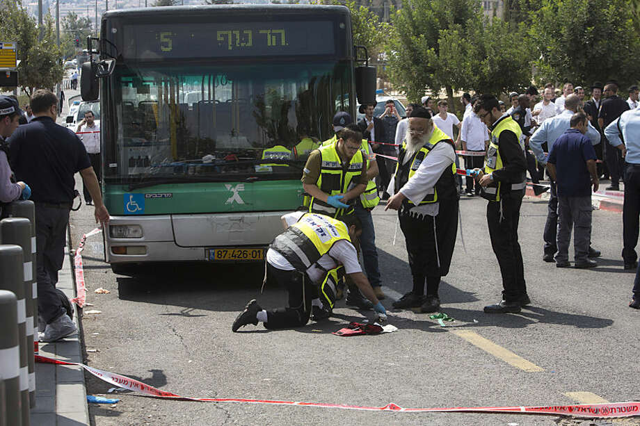 Israeli ZAKA emergency response members clean the scene of a stabbing attack in Jerusalem, Thursday, Oct. 8, 2015. A Palestinian stabbed a Jewish seminary student in Jerusalem on Thursday as the Israeli prime minister barred all Cabinet ministers and lawmakers from visiting a sensitive holy site in the Old City in an effort to calm tensions that have gripped the country for weeks. (AP Photo/Sebastian Scheiner)