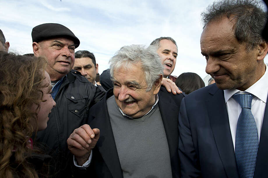Argentina's presidential candidate and Buenos Aires provincial Governor Daniel Scioli, right, and Uruguay's former President Jose Mujica, center, smile at a girl during a visit to a rural school in Magdalena, Buenos Aires province, Argentina, Wednesday, Oct. 7, 2015. Argentina will hold general elections on Oct. 25. (AP Photo/Natacha Pisarenko)