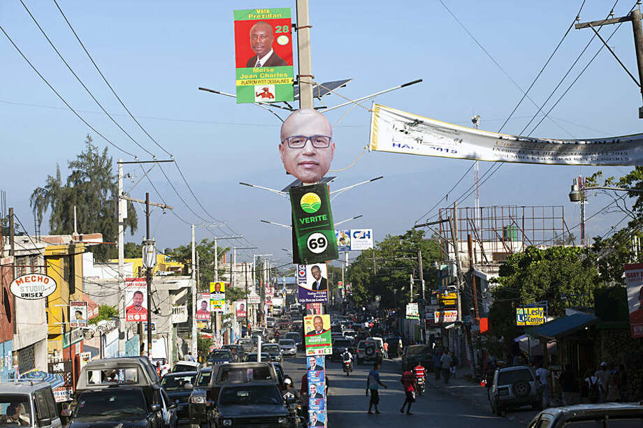 Campaign posters promoting presidential candidates line Delmas Street, in Port-au-Prince, Haiti, Wednesday, Oct. 7, 2015. In the first round of Haiti's presidential vote on Oct. 25, voters will choose from a field of 54 candidates. (AP Photo/Dieu Nalio Chery)