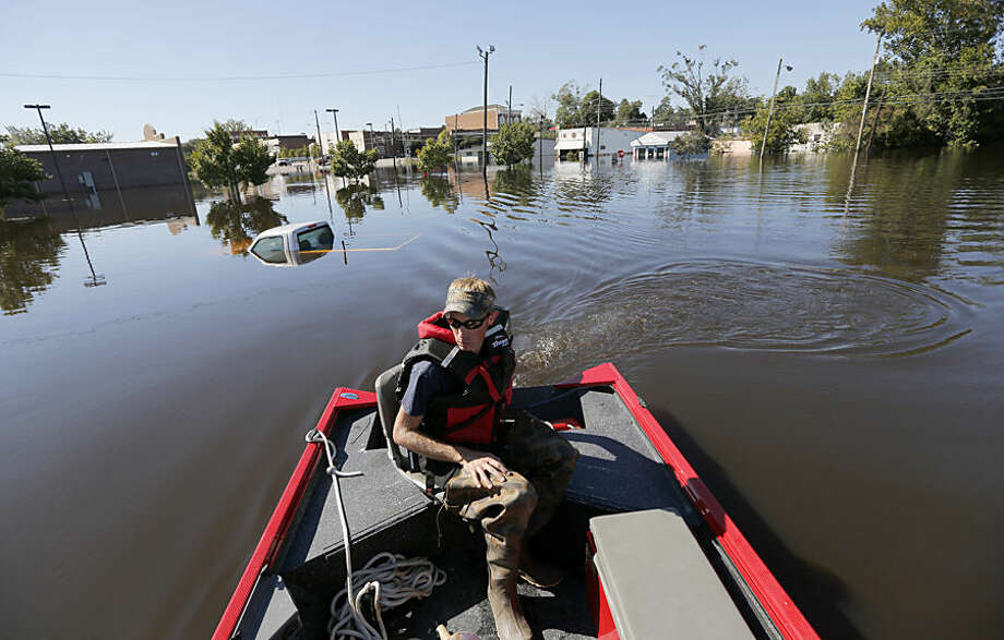 "Greg Ward, with the Kingstree Fire Department, searches for unstable propane tanks in downtown Kingstree, S.C., Wednesday, Oct. 7, 2015. ""Were pretty much an island right now,"" Ward said of his small city. (AP Photo/Mic Smith)"