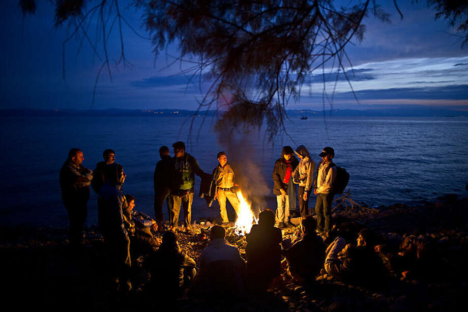 Syrian and Afghan refugees warm themselves and dry their clothes around a fire after arriving on a dinghy from the Turkish coast to the northeastern Greek island of Lesbos, early Wednesday, Oct. 7, 2015. (AP Photo/Muhammed Muheisen)
