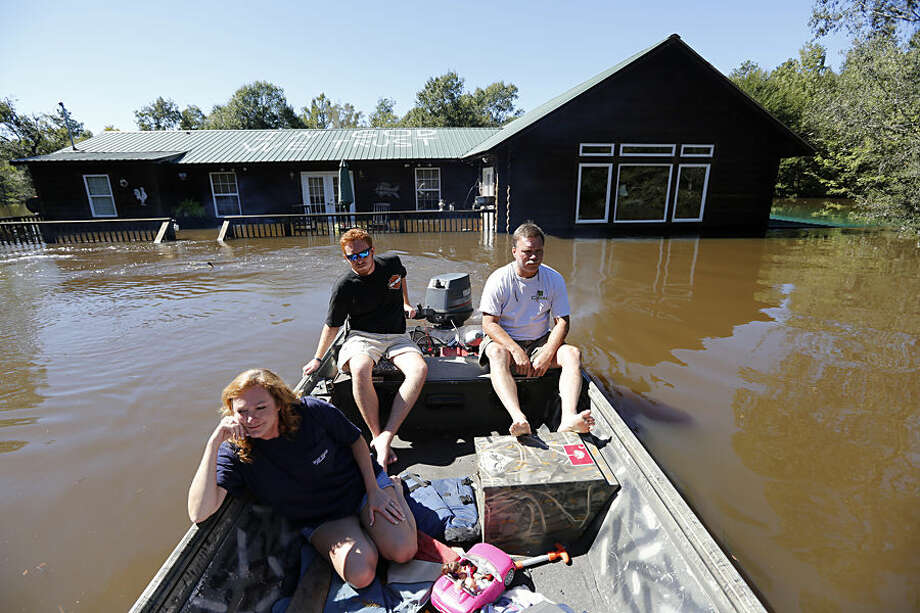 "Lisa Britton, left, and her husband Jody, right, leave their house on the Black River with the son, J.D., driving the boat, near Kingstree, S.C., Wednesday, Oct. 7, 2015. What is visible of the house is the second floor that is 22 feet high from the ground. Their message on the roof ""in God we Trust"" was put their before the floodwaters came. (AP Photo/Mic Smith)"