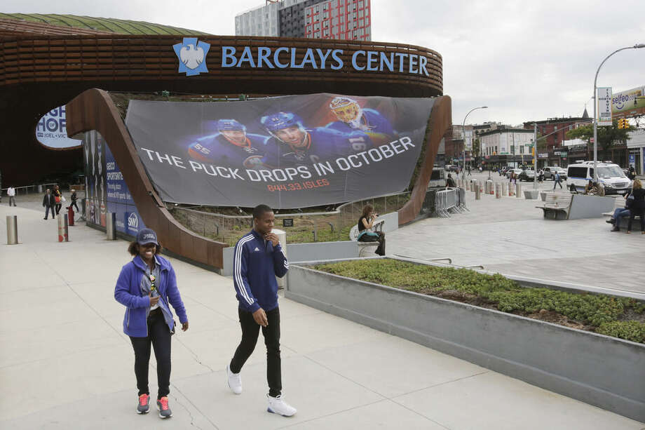 People walk by the Barclays Center, Thursday, Oct. 8, 2015 in the Brooklyn borough of New York. The New York Islanders hockey team, who formerly played at Nassau Coliseum in Uniondale, N.Y., will now call Brooklyn home when they open the 2015-2016 season on Friday against the Chicago Blackhawks. (AP Photo/Mark Lennihan)