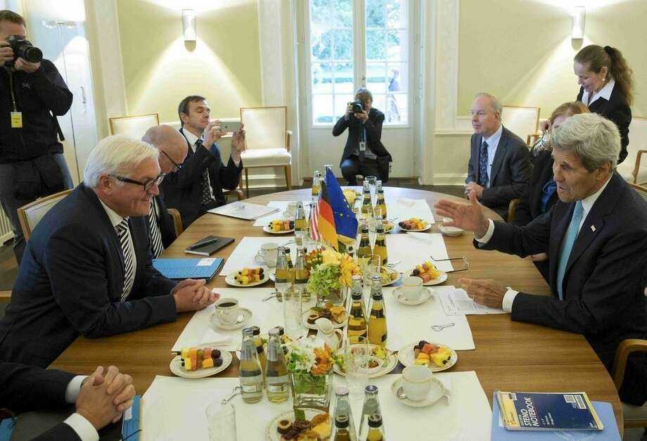 German Foreign Minister Frank-Walter Steinmeier , left, speaks with U.S. Secretary of State ,John Kerry, during their meeting in the German foreign ministry's guesthouse ,Villa Borsig, at lake Tegel in Berlin, Germany, Sunday Sept. 20, 2015. (Axel Schmidt /Pool Photo via AP)