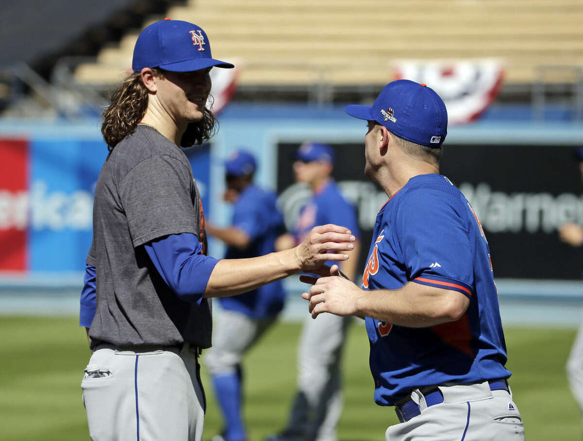 New York Mets starting pitcher Jacob deGrom, left, greets third baseman David Wright during batting practice in preparation for the National League Division Series against the Los Angeles Dodgers that is set to begin on Friday, Thursday, Oct. 8, 2015, in Los Angeles. (AP Photo/Chris Carlson)