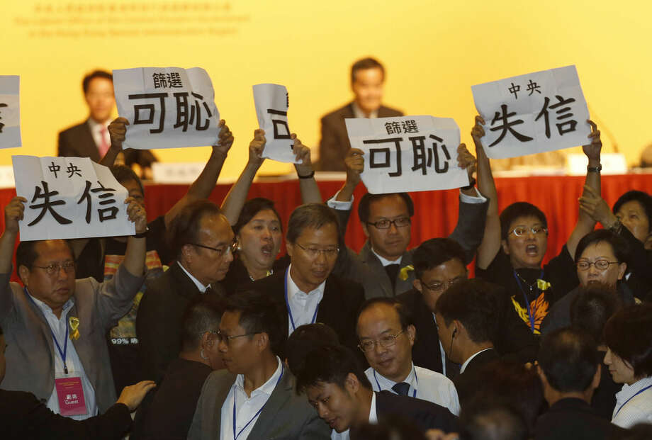 "Pro-democracy lawmakers display placards against Li Fei, deputy secretary general of the National People's Congress' Standing Committee, during a briefing session in Hong Kong Monday, Sept. 1, 2014. Hong Kong pro-democracy legislators have disrupted the Beijing official's speech as he sought to explain a decision to tightly limit voting reforms for the southern Chinese financial hub. The placards read ""Break a promise"" and ""Shameful."" (AP Photo/Kin Cheung)"