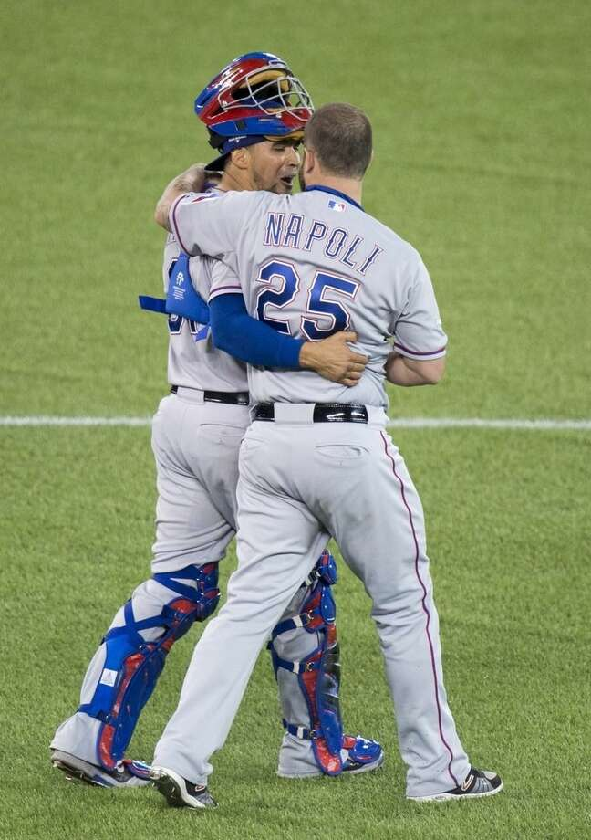 Texas Rangers Robinson Chirinos, left, and Mike Napoli celebrate their 5-3 win of Game 1 of the American League Division Series against the Toronto Blue Jays in Toronto on Thursday, Oct. 8, 2015. (Darren Calabrese/The Canadian Press via AP) MANDATORY CREDIT