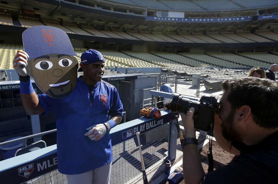New York Mets center fielder Yoenis Cespedes poses with his caricature after a workout in preparation for the National League Division Series against the Los Angeles Dodgers that is set to begin on Friday, Thursday, Oct. 8, 2015, in Los Angeles. (AP Photo/Chris Carlson)
