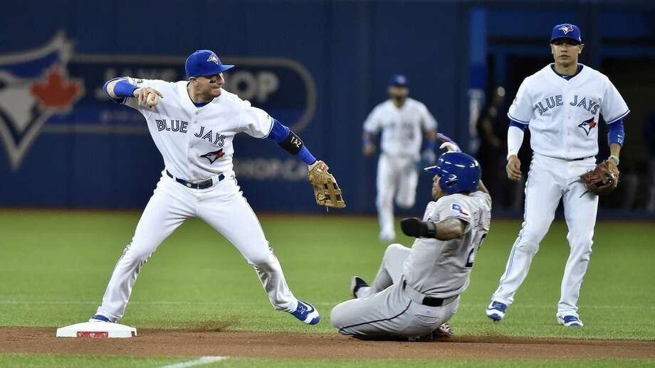 Toronto Blue Jays' shortstop Troy Tulowitzki forces Texas Rangers' Adrian Beltre at second base before throwing to first base for the double play during the first inning in Game 1 of baseballs American League Division Series in Toronto on Thursday, Oct. 8, 2015. (Nathan Denette/The Canadian Press via AP)