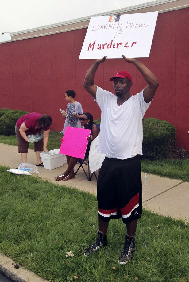 "In this Aug. 23, 2014 photo, Lamont Jones holds up a sign reading ""Darren Wilson is a Murderer,"" in St. Louis. Jones was reacting to a rally supporting Wilson, the white officer who shot unarmed, black 18-year-old Michael Brown in Ferguson, Mo. Like many Americans, Jones has formed concrete opinions about the case. (AP Photo/Jesse Washington)"