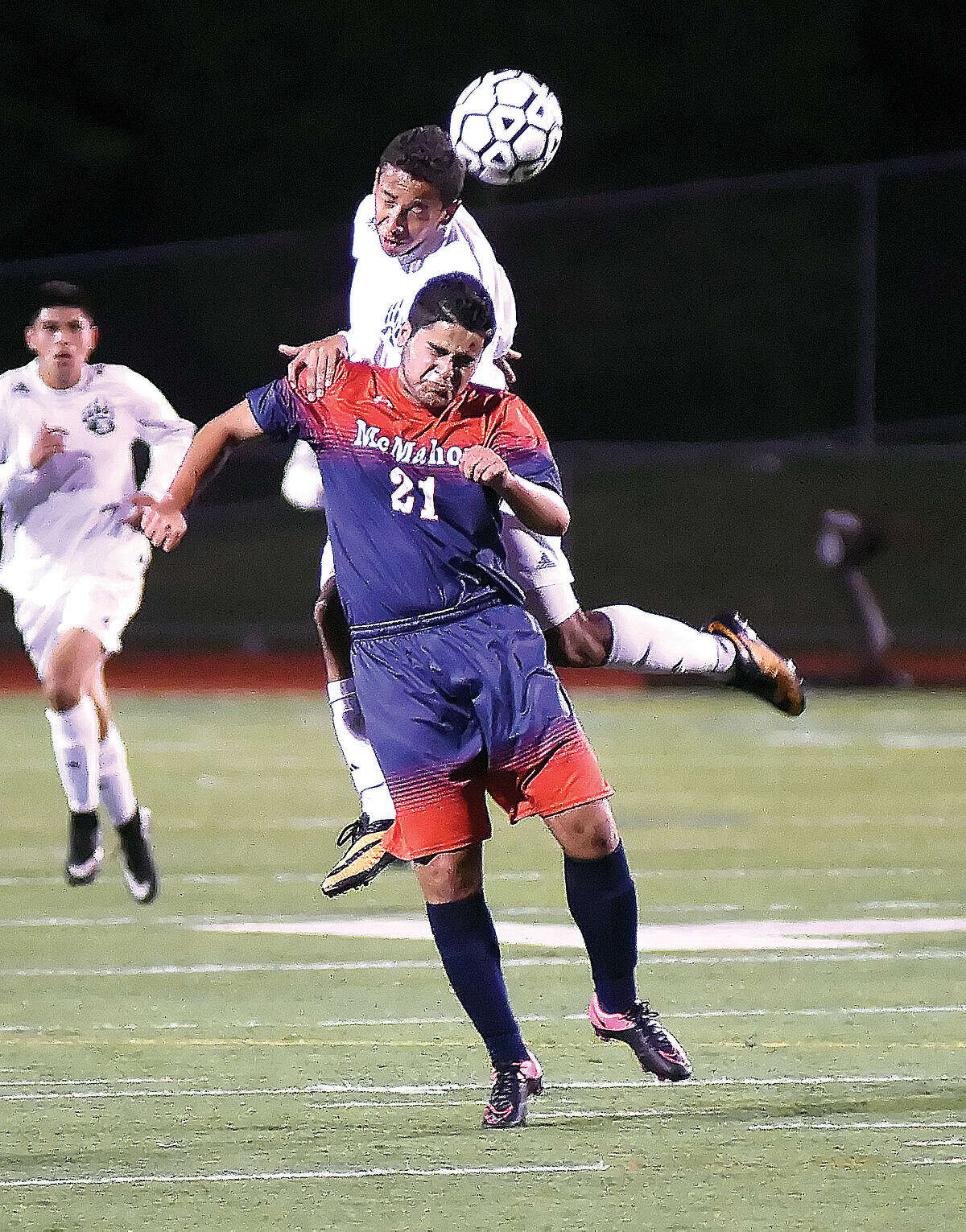 Hour photo/John Nash - Norwalk's Sebastian Echeverri, rear, heads the ball before McMahon's Abdullah Mawla can play it during Thursday's FCIAC boys soccer game at Testa Field in Norwalk. The two teams battled to a 1-1 tie.
