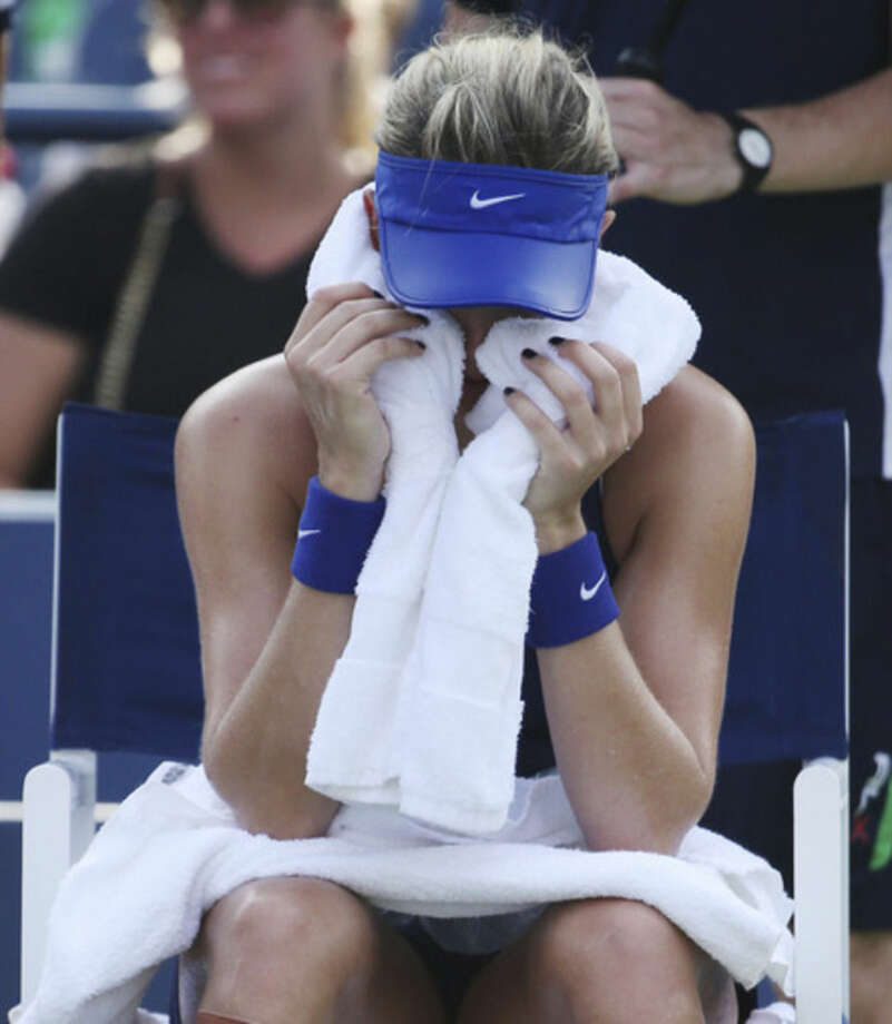 Eugenie Bouchard, of Canada, wraps her head in an ice-packed towel between games against Ekaterina Makarova, of Russia, during the fourth round of the 2014 U.S. Open tennis tournament, Monday, Sept. 1, 2014, in New York. (AP Photo/John Minchillo)