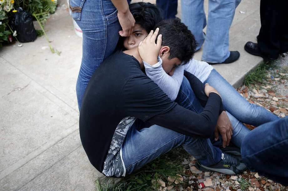 Relatives weep during the burial of four members of the Valenzuela Family who died in a mudslide, in the Santa Catarina Pinula cemetery on the outskirts of Guatemala City, Sunday, Oct. 4, 2015. Rescue workers recovered more bodies after a hillside collapsed on homes late Thursday, while more are feared still buried in the rubble. (AP Photo/Moises Castillo)