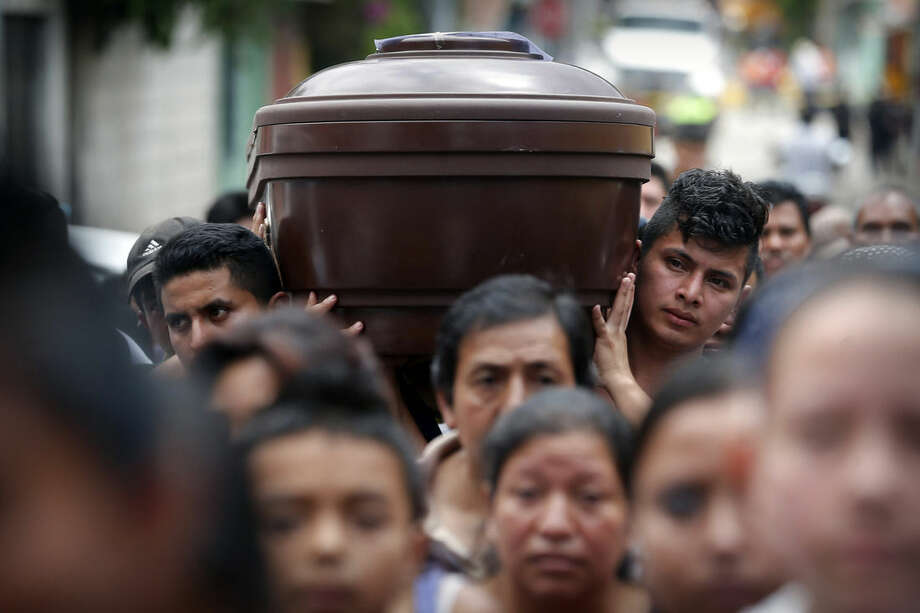 People carry the coffin of Amilcar Estrada, who died in a mudslide, to the Santa Catarina Pinula cemetery on the outskirts of Guatemala City, Sunday, Oct. 4, 2015. Rescue workers recovered more bodies after a hillside collapsed on homes late Thursday, while many more are feared still buried in the rubble. (AP Photo/Moises Castillo)