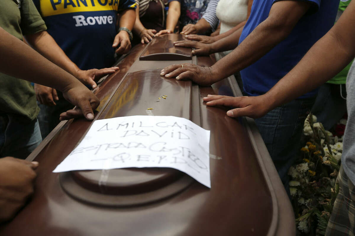 Relatives place their hands on the coffin of Amilcar Estrada, who died in a mudslide, during his burial at the Santa Catarina Pinula cemetery on the outskirts of Guatemala City, Sunday, Oct. 4, 2015. Hope faded Sunday for finding any survivors of a mudslide that killed at least 87 people as authorities said that hundreds more may still be missing. (AP Photo/Moises Castillo)