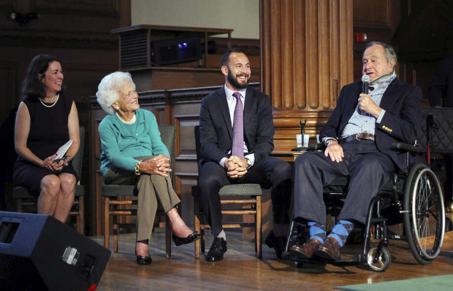 FILE - In this Wednesday, Sept. 30, 2015 file photo provided by Phillips Academy, former President George H.W. Bush, right, speaks, during a visit to Phillips Academy in Andover, Mass., for a screening of a documentary about the former president. On stage with Bush are Mary Kate Cary, left, executive producer of the documentary, former first lady Barbara Bush, second from left, and Evan Sisley, an aide to alumnus (Neil Evans/Phillips Academy via AP, File)