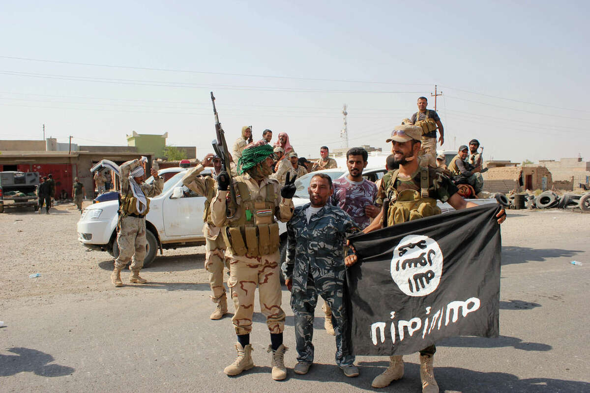 In this Monday, Sept. 1, 2014 photo, Shiite militiamen hold the flag of the Islamic State group they captured, during an operation outside Amirli, some 105 miles (170 kilometers) north of Baghdad, Iraq. Under the shadow of the Islamic State group threat, governments from France to Indonesia are moving aggressively to block would-be jihadis from taking their fight to Syria and Iraq. New laws make it easier to seize passports. Suspected fighters are being plucked from planes. Authorities are blocking finances and shutting down radical mosques. Behind the scenes, Western intelligence agencies are striving to stay ahead of tech-savvy radicalized Muslims by pressuring Silicon Valley firms to wipe extremist content from websites and toying with new technologies to identify returning fighters at the border. Britain has taken a particularly active role in censoring content deemed to break the country?'s strict rules against extremist propaganda. U.K. officials recently revealed it had been granted ?