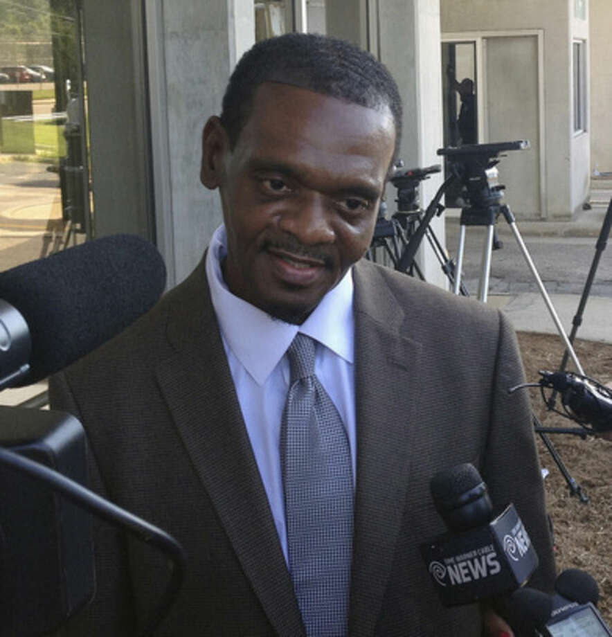 James McCollum, facing camera, walks from court following his release from Central Prison in Raleigh, N.C., on Wednesday, Sept. 3, 2014. Henry McCollum spent more than 30 years on death row for a rape and murder he didn't commit. (AP Photo/Michael Biesecker)