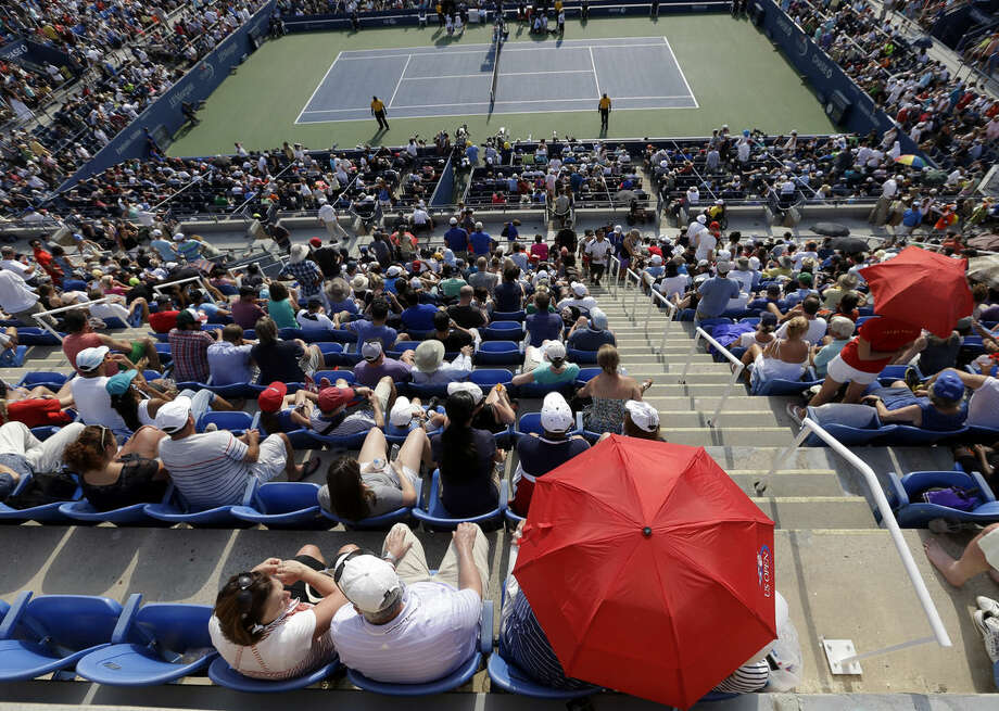 Spectator takes cover under an umbrella during the fourth round match between Eugenie Bouchard, of Canada, and Ekaterina Makarova, of Russia, in the 2014 U.S. Open tennis tournament Monday, Sept. 1, 2014, in New York. (AP Photo/Darron Cummings)
