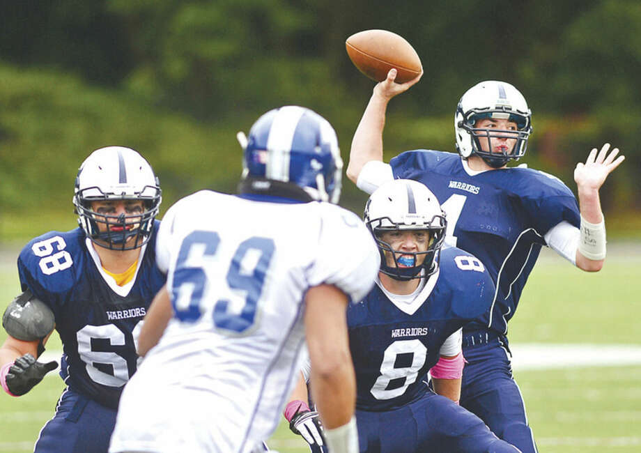 Hour photo/Erik TrautmannWilton High School football quarterback R.J. Romeo, far right, readies to throw for a touchdown as the Warriors battle Fairfield Ludlowe in Wilton Saturday. Wilton players Nick Pica (68) and Joe McFadden supply blocking.