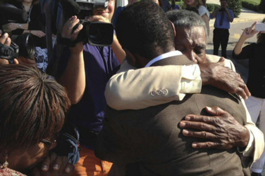 James McCollum, facing camera, embraces his son Henry following the younger man's release from Central Prison in Raleigh, N.C., on Wednesday, Sept. 3, 2014. Henry McCollum spent more than 30 years on death row for a rape and murder he didn't commit. McCollum's Step mother Priscilla McCollum is at left. (AP Photo/Michael Biesecker)