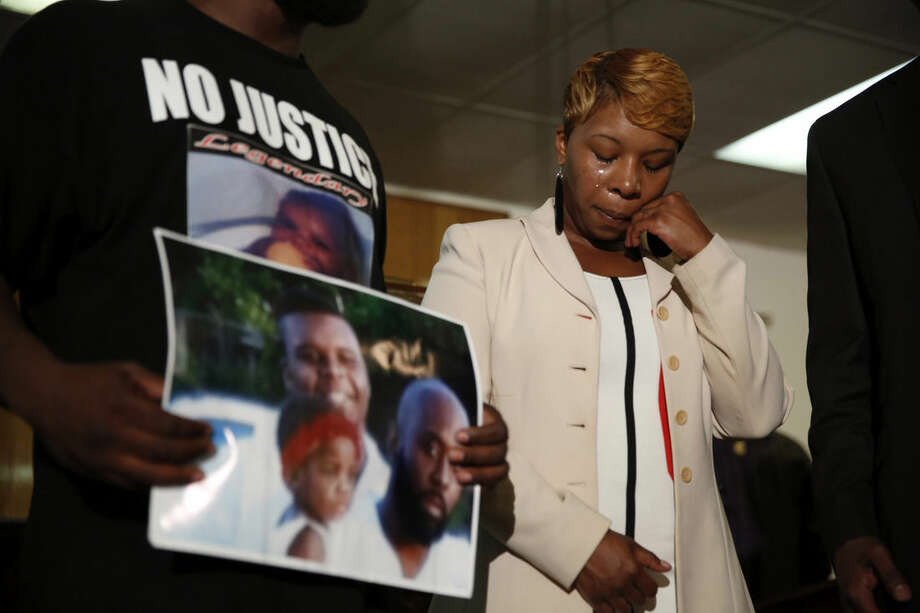 FILE - In this Aug. 11, 2014 file photo, Lesley McSpadden, the mother of 18-year-old Michael Brown, wipes away tears as Brown's father, Michael Brown Sr., holds up a family picture of himself, his son, top left, and a young child during a news conference in Jennings, Mo. Lingering questions about Michael Brown could be answered Wednesday as two news organizations seek the release of any possible juvenile records for the unarmed 18-year-old who was shot by a police officer last month.(AP Photo/Jeff Roberson, File)