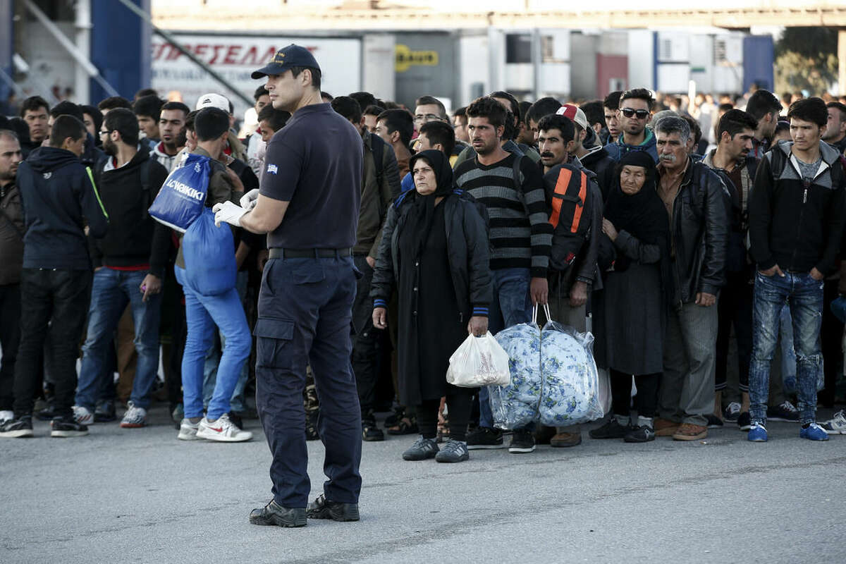 A policeman stands guard in front of a queue by migrants and refugees waiting to get on buses which will transfer them at a metro station after their arrival from the Greek island of Lesbos at the Athens' port of Piraeus, Sunday, Oct. 4, 2015. The U.N. refugee agency is reporting a