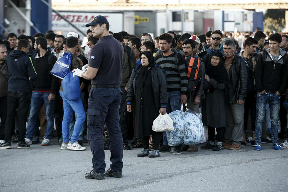 "A policeman stands guard in front of a queue by migrants and refugees waiting to get on buses which will transfer them at a metro station after their arrival from the Greek island of Lesbos at the Athens' port of Piraeus, Sunday, Oct. 4, 2015. The U.N. refugee agency is reporting a ""noticeable drop"" this week in arrivals of refugees by sea into Greece _ as the total figure for the year nears the 400,000 mark. Overall, the UNHCR estimates 396,500 people have entered Greece via the Mediterranean this year with seventy percent of them are from war-torn Syria. (AP Photo/Yorgos Karahalis)"