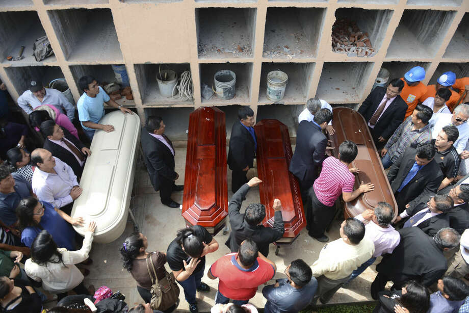 People surround the coffins of four members of the Valenzuela family who died in a mudslide, as they are put to rest in the Santa Catarina Pinula cemetery on the outskirts of Guatemala City, Sunday, Oct. 4, 2015. Hope faded Sunday for finding any survivors of a mudslide that killed at least 87 people as authorities said that hundreds may still be missing. (AP Photo/Oliver de Ros)