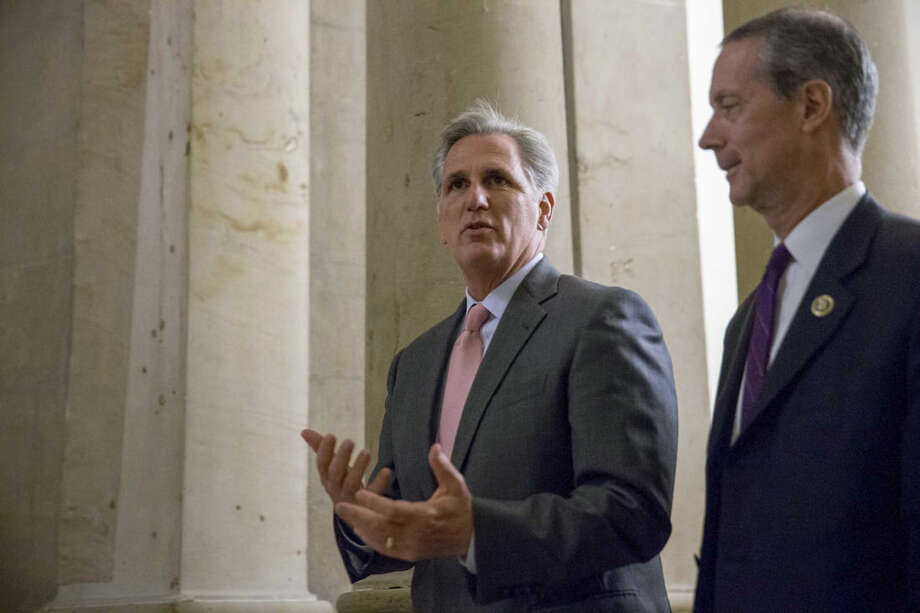 FILE - In this Sept. 30, 2015 file photo, House Majority Leader Kevin McCarthy of Calif., left, walks on Capitol Hill in Washington. McCarthy says he regrets comments suggesting the House special committee on Benghazi has political goals. McCarthy says he never intended to make that suggestion. He says the purpose of the committee is to find out the truth and it has nothing to do with politics. (AP Photo/Andrew Harnik, File)