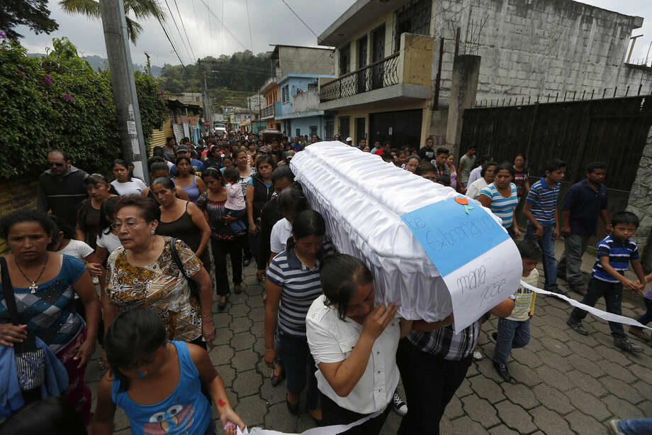 """People carry the white coffin of ten-year-old Maria Jose Estrada, and her uncle Amilcar Estrada, back, who both died in a mudslide, to the Santa Catarina Pinula cemetery on the outskirts of Guatemala City, Sunday, Oct. 4, 2015. The sign on the white coffin reads in Spanish """"We miss you Maria Jose."""" Rescue workers recovered more bodies Saturday after a hillside collapsed on homes late Thursday, while more are feared still buried in the rubble. (AP Photo/Moises Castillo)"""