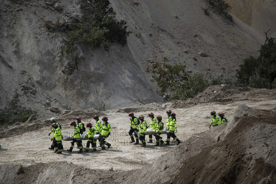 Rescuers carry bodies recovered from the site of a mudslide in Cambray, a neighborhood in the suburb of Santa Catarina Pinula, on the outskirts of Guatemala City, Sunday, Oct. 4, 2015. Hope faded Sunday for finding any survivors of a mudslide that killed at least 87 people as authorities said that hundreds more may still be missing. (AP Photo/Luis Soto)