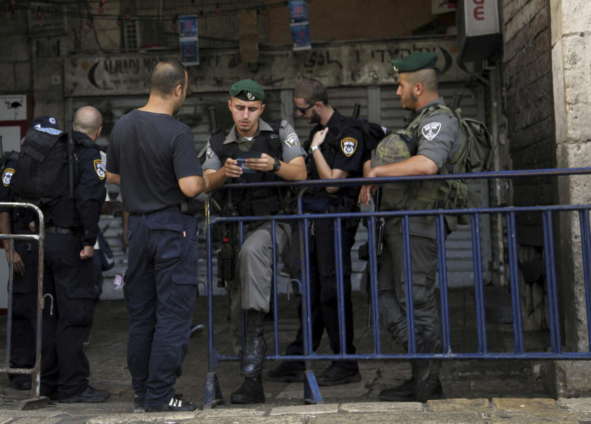 An Israeli border policeman checks papers at the entrance to the Old City in Jerusalem on Sunday, Oct. 4, 2015. Israeli police barred Palestinians from Jerusalem's Old City on Sunday in response to stabbing attacks that killed two Israelis and wounded three others, as Israeli Prime Minister Benjamin Netanyahu vowed a