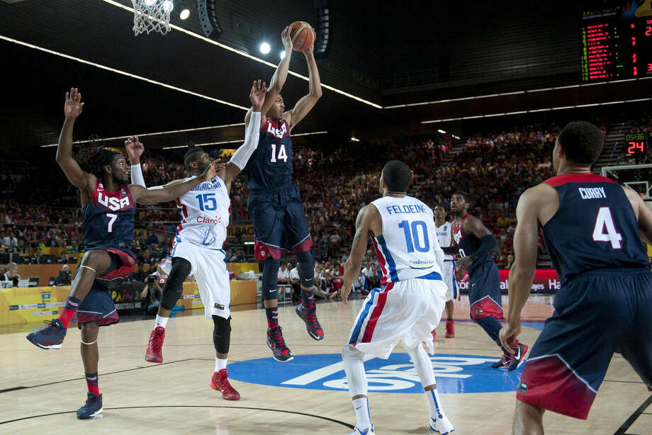 United States's Anthony Davis, center, controls the ball in front Dominican Republic's Jack Martinez during the Group C Basketball World Cup match, in Bilbao northern Spain, Wednesday, Sept. 3, 2014. The 2014 Basketball World Cup competition take place in various cities in Spain from Aug. 30 to Sept. 14. (AP Photo/Alvaro Barrientos)
