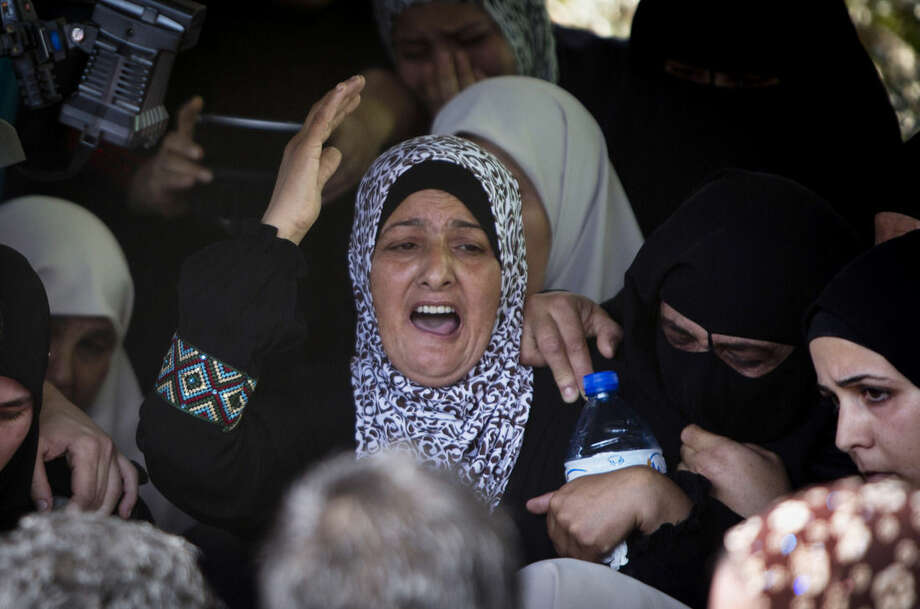 Relatives of Palestinian youth Huthaifa Suleiman, 18, mourn during his funeral in the Bal'a village near the West Bank city of Tulkarem, Monday, Oct. 5, 2015. Suleiman was killed in clashes with Israeli soldiers in the West Bank on Monday, according to a doctor at Tulkarem hospital, as fears spread of a further escalation in violence that has already killed several Israeli civilians and wounded scores of Palestinian protesters over the past days. (AP Photo/Majdi Mohammed)