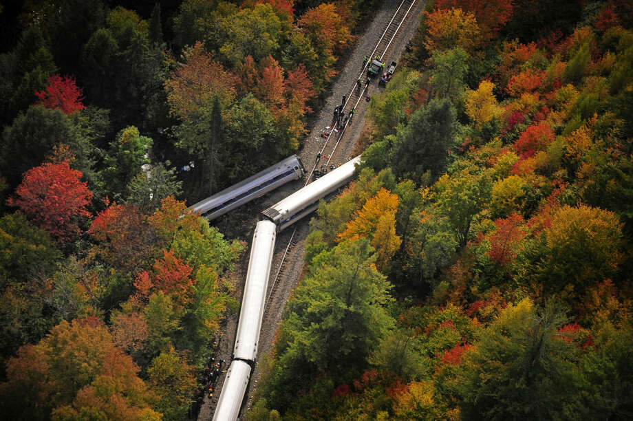 In this aerial photo railroad cars from a derailed Amtrak passenger train are surrounded by foliage, Monday, Oct. 5, 2015, in Northfield, Vt. The train, the Vermonter, was headed from Vermont to Washington, D.C., when it apparently struck rocks that were on the tracks. No life-threatening injuries were reported. (Stefan Hard/Barre-Montpelier Times Argus via AP)