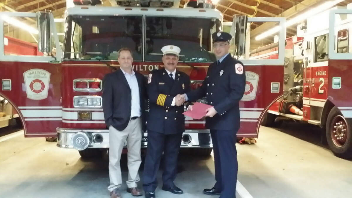 Firefighter Michael Blatchey accepts a commendation from Fire Chief Ron Kanterman for his life-saving efforts last month at the Wilton Chamber of Commerce's Street Fair, where Blatchley helped a Wilton manwho severely injured his wrist.
