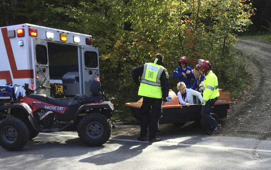 Emergency first responders assist a woman, center, as she is transferred to an ambulance from a trailer attached to an all-terrain vehicle near the site of an Amtrak train derailment, Monday, Oct. 5, 2015, in Roxbury, Vt. The Amtrak train, headed from Vermont to Washington, D.C., derailed in central Vermont on Monday after apparently striking rocks that were on the tracks about 20 miles southwest of the capital, Montpelier. (AP Photo/Wilson Ring)