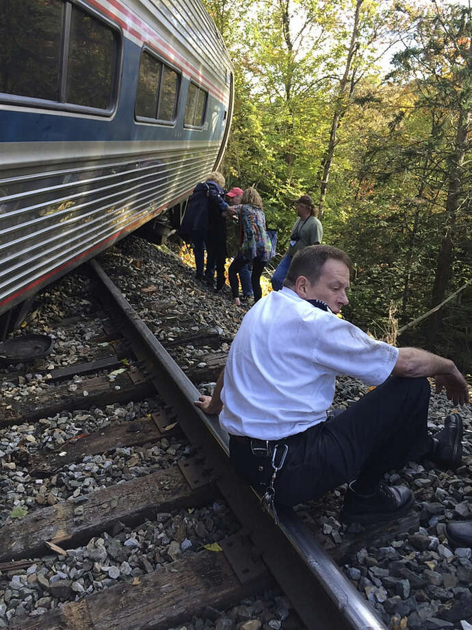 In this photo provided by Brian Bell, a train conductor sits next to an Amtrak train after it derailed, Monday, Oct. 5, 2015, near Roxbury, Vt., about 20 miles southwest of Montpelier, Vt. The train, the Vermonter, was headed from Vermont to Washington, D.C., when it apparently struck rocks that were on the tracks. No life-threatening injuries were reported. (Cathy Bell/Courtesy of Brian Bell via AP)